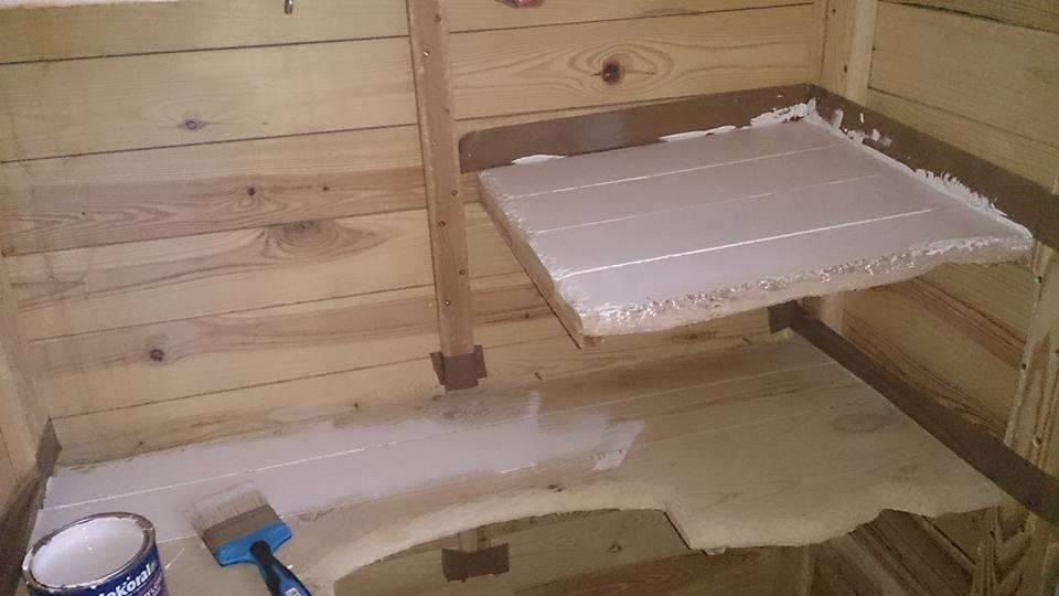 Zabezpieczenie klatki za pomocą taśmy przed malowaniem półek.